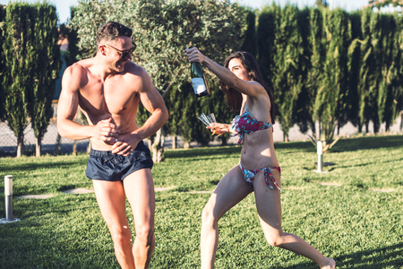 Girl running after her friend holding bottle of champagne and glasses in her hands on sunny day.