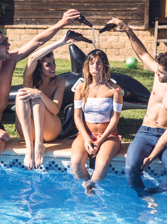 Group of friends pouring water on one girl while sitting on poolside and laughing.