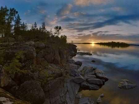 Sunset at stony shore of Ladoga lake, Russia