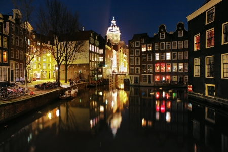 Evening view on the channels of Amsterdam and St. Nicolas Church (St. Nicolaaskerk), Netherlands