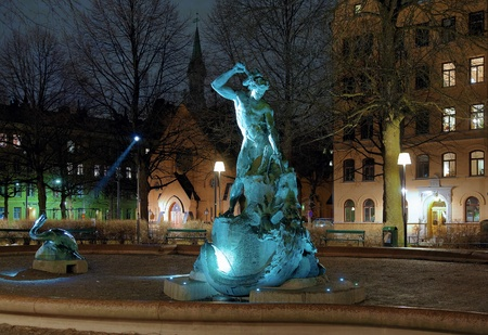 Tors fiske (Thors Fishing) - fountain in Stockholm and St. Paul church at evening, Sweden photo