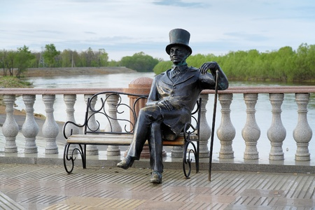 Sculpture of man in a top hat with a cane sitting on a bench on the Bira river embankment in Birobidzhan, Far East, Russia