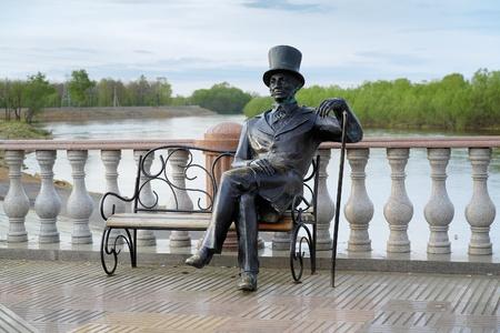 messze: Szobor az ember cilinderben bottal ül egy padon a Bira folyó partján a Birobidzhan, Távol-Kelet, Oroszország