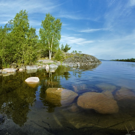 Shallow water at the stone shore of Ladoga lake, Russia photo