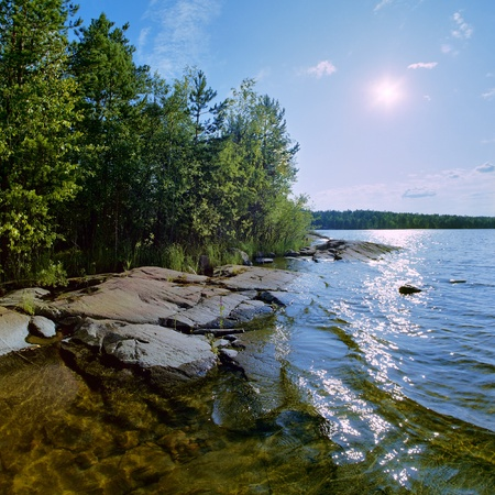 Sun and stony shore of Ladoga lake, Russia photo