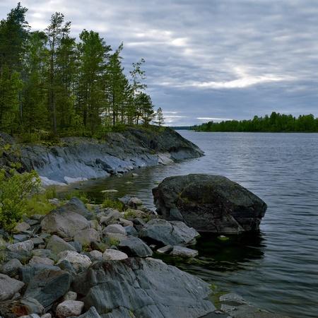 Stony shore of Ladoga lake at evening, Karelia, Russia photo