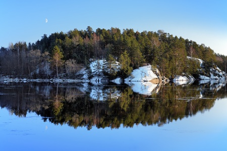 An island with pine trees reflected in the lake in winter, Finland photo