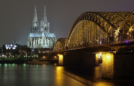 Night view on Cologne Cathedral and Hohenzollern Bridge over the Rhine river, Germany Standard-Bild