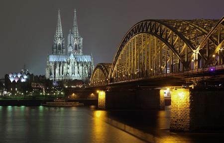 Nacht uitzicht op de Dom van Keulen en Hohenzollern Brug over de rivier de Rijn, Duitsland