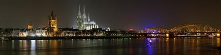 Nacht panorama van Keulen met Great St. Martin Church, Dom van Keulen en Hohenzollern Bridge uit oever van de Rijn, Duitsland
