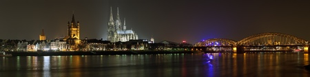 cologne: Night panorama of Cologne with Great St  Martin Church, Cologne Cathedral and Hohenzollern Bridge from bank of the Rhine river, Germany