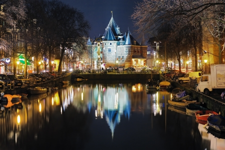 Evening view on the De Waag, former city gates of St  Anthony  from channel in Amsterdam, Netherlands