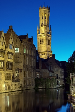 Evening view of Belfort tower from the canal in Bruges, Belgium photo