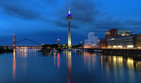 Evening view of the Media Harbor in Dusseldorf with Rheinturm TV tower and Buildings of Neuer Zollhof, Germany Stock Photo