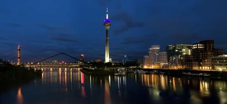 Evening panorama of the Media Harbor in Dusseldorf with Rheinturm TV tower and Buildings of Neuer Zollhof, Germany