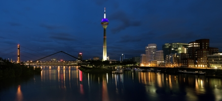 westfalen: Evening panorama of the Media Harbor in Dusseldorf with Rheinturm TV tower and Buildings of Neuer Zollhof, Germany