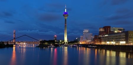 Evening panorama of the Media Harbor in Dusseldorf with Rheinturm TV tower and Buildings of Neuer Zollhof, Germany