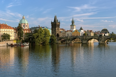 Prague, View of Charles Bridge with Old Town bridge tower and Dome of the church of Saint Francis of Assisiat the end of a summer day, Czech Republic photo