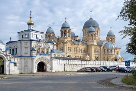 Nikolay Monastery in Verkhoturye with Cathedral of Exaltation of the Holy Cross in neo-byzantine style and Gate church of Simeon and Anna in old russian style, Russia photo