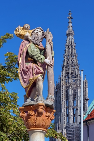 Statue of St Christopher carrying the Christ Child and Tower of the Ulm Minster, Ulm, Germany photo