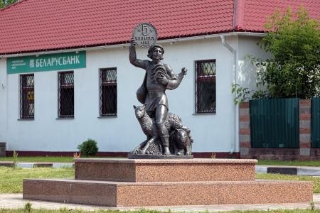Sculptuur van een boer met boerderijdieren en grote oude Russisch muntstuk in zijn arm in de buurt van het kantoor van Belarusbank in Lepel, Wit-Rusland