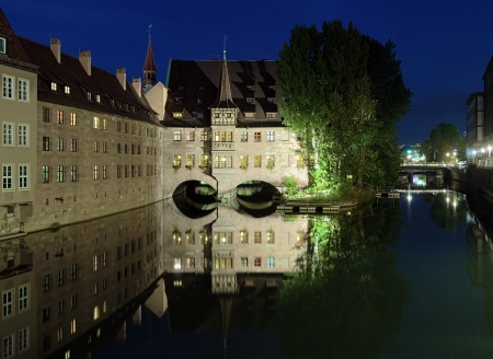 Evening view of the Heilig-Geist-Spital  Holy Spirit Hospital  from the river Pegnitz in Nuremberg, Germany photo