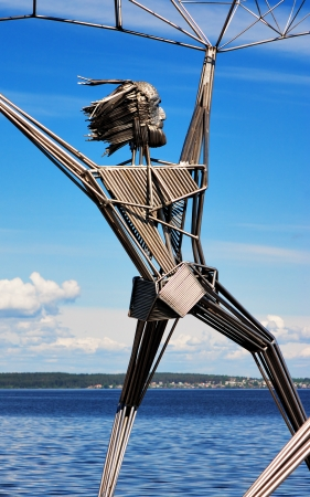 onega: Fisher with the fishnet - fragment of sculpture on the embankment of Lake Onega in Petrozavodsk, Russia