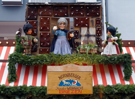 The signboard and dolls above the stall with christmas pretzels and honey-cakes at the Children