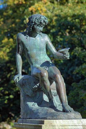 bacchus: Sitting Bacchus by swedish sculptor Erik Gustaf Gothe near the Rosendal Palace on Djurgarden island of Stockholm, Sweden Stock Photo