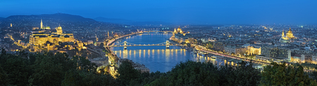 building a chain: Evening panorama of Budapest, view from Gellert Hill, Hungary. The panorama shows: Buda Castle, Danube river with Szechenyi Chain Bridge, Hungarian Parliament Building and St. Stephens Basilica.