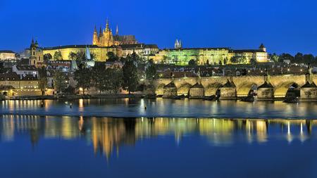 castle district: Prague, Czech Republic. Evening view of the Prague Castle with St. Vitus Cathedral, Castle district, Mala Strana district with St. Nicholas Church, and Charles Bridge with Mala Strana Bridge Towers.