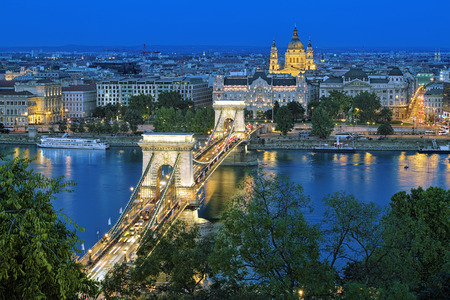 szechenyi: Evening view of Szechenyi Chain Bridge over Danube and St. Stephens Basilica in Budapest, Hungary. View from Royal Palace in Buda Castle.