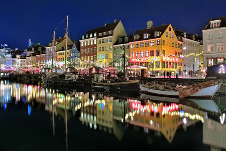 entertainment district: COPENHAGEN, DENMARK - DECEMBER 12, 2015: Evening view of Nyhavn. Nyhavn is a waterfront, canal and entertainment district with brightly coloured 17th century townhouses and bars, cafes and restaurants Editorial