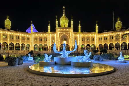COPENHAGEN, DENMARK - DECEMBER 14, 2015: The Christmas installation with Swans in front of the Moorish Palace in Tivoli Gardens at night. Since 2008 in the palace located the five-star hotel Nimb.