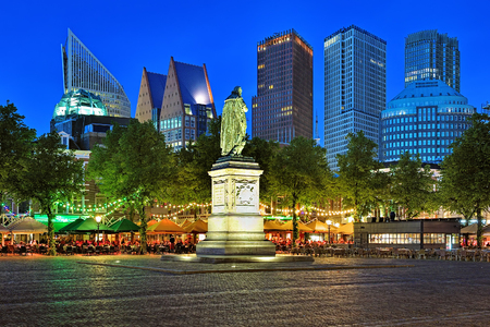 THE HAGUE, NETHERLANDS - MAY 23, 2015: Het Plein Square with the statue of William the Silent on the background of the citys skyscrapers in the evening. The square is known for its many restaurants.