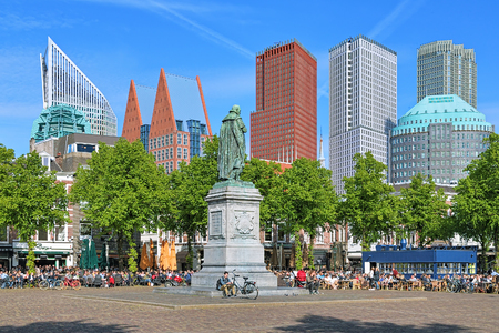 plein: THE HAGUE, NETHERLANDS - MAY 21, 2015: Het Plein Square with the statue of William the Silent on the background of the citys skyscrapers. The square is known for its many restaurants. Editorial