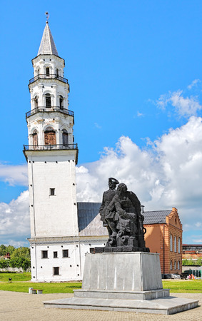 konstantin: NEVYANSK, RUSSIA - JULY 24, 2015: Monument of Peter the Great and Nikita Demidov on the background of the Leaning Tower. The monument by sculptor Konstantin Grunberg was unveiled on July 19, 2002. Stock Photo