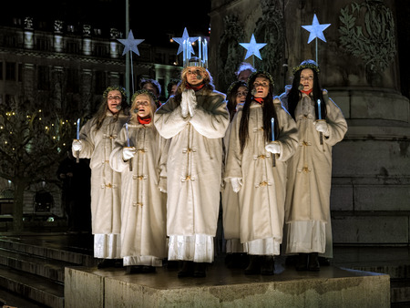MALMO, SWEDEN - DECEMBER 13, 2015: Lucia and her entourage sing a song on the Main square during the celebration of St. Lucys Day. Malmos Lucia 2015 was elected Matilda Strom, a service dog handler.