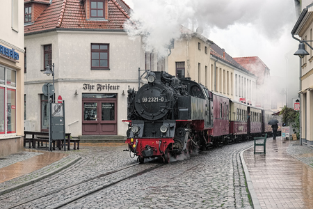 narrowgauge: BAD DOBERAN, GERMANY - OCTOBER 22, 2016: Steam train of the narrow-gauge railway Molli rides through the street Mollistrasse in rainy day. The railway was put into operation on July 9, 1886.