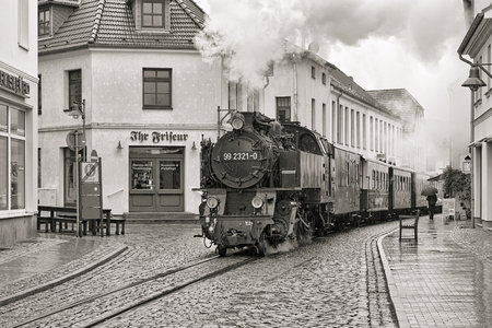 narrowgauge: BAD DOBERAN, GERMANY - OCTOBER 22, 2016: Steam train of the narrow-gauge railway Molli rides through the street Mollistrasse in rainy day. The railway was put into operation on July 9, 1886. Black and White image.