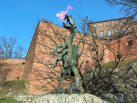 KRAKOW, POLAND - DECEMBER 17, 2016: Wawel Dragon Statue breathing fire at the foot of the Wawel Hill. The statue was designed by the Polish sculptor Bronislaw Chromy and installed in 1972.
