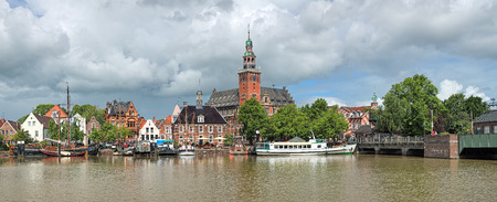 leer: Leer, Germany. Panoramic view from Leda river on City Hall in Dutch Renaissance style, Old Weigh House in Dutch classical Baroque style, Tourist Harbor and Bridge of Erich vom Bruch.