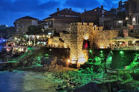 SOZOPOL, BULGARIJE - SEPTEMBER 3, 2015: Zuidelijke Vestingsmuur en Toren van Oude Stad met geelgroene verlichting in avond. Sozopol is de beroemde badplaats aan de kust van de Zwarte Zee. Stockfoto - 76378272