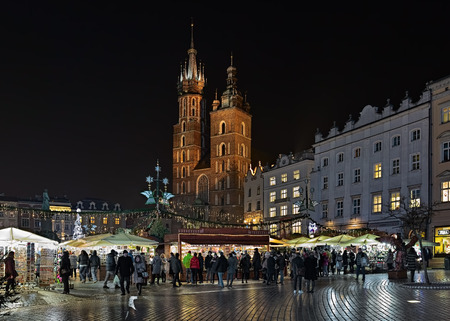 KRAKOW, POLAND - DECEMBER 16, 2016: Christmas market on the Main square (Rynek Glowny) in front of St. Marys Basilica. The market starts in the last week of November and lasts through December 26th.