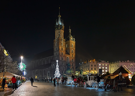 Christmas market and row of horse carriages on the Main Square of Krakow in front of the St. Marys Basilica in night, Poland Stock Photo