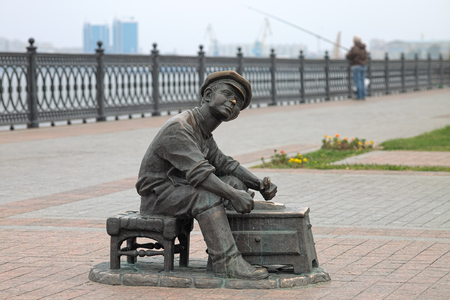 ASTRAKHAN, RUSSIA - OCTOBER 20, 2017: Sculpture of shoeshine boy from the Soviet comedy film It Cant Be! on the embankment of Volga River. The sculpture was unveiled on August 24, 2012. Editorial