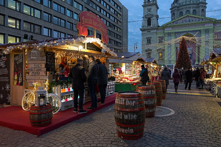 BUDAPEST, HUNGARY - DECEMBER 5, 2016: Market stalls with drinks, sweets and gifts at the Christmas Market and Advent Feast in front of the St. Stephens Basilica in evening.