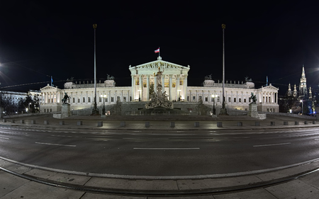 Panorama of the Austrian Parliament Building in Vienna in night. The building was built in 1874-1883. The Pallas Athene Fountain in front of the building was erected between 1893 and 1902.