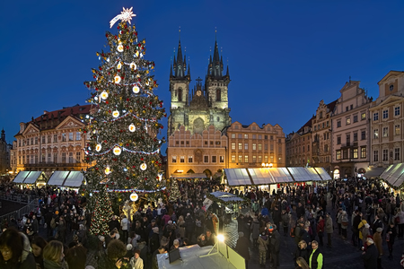 PRAGUE, CZECH REPUBLIC - DECEMBER 7, 2017: Christmas market on the Old Town Square in twilight. The image shows the city's main Christmas tree with nativity scene, and Church of Our Lady before Tyn. Publikacyjne