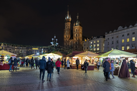 KRAKOW, POLAND - DECEMBER 15, 2016: Christmas market at the Main square (Rynek Glowny) in front of St. Marys Basilica. The market starts in the last week of November and lasts through December 26th.